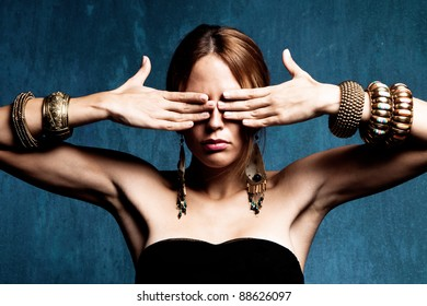 woman with hands on the eyes and lot of bracelets, studio shot