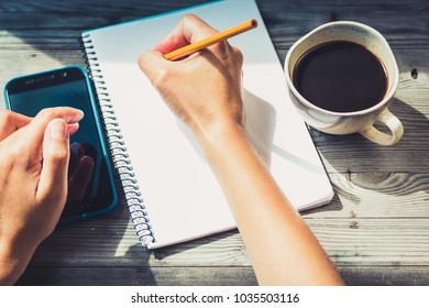 Woman hands on grey wooden table with cup of coffee,paper notepad,phone. dark vintage toned image. Business concept.