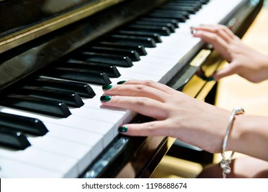Woman hands on the piano keys.