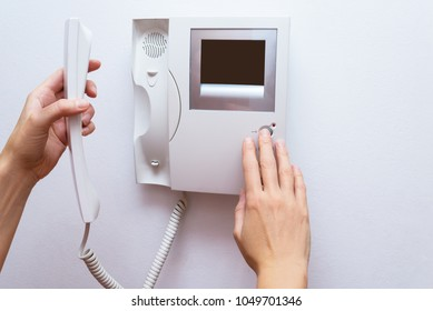 Woman hands opening door through intercom