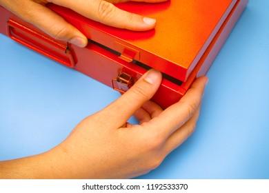 Woman hands opening orange metal box. Close-up.