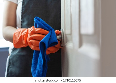 Woman hands in orange rubber gloves cleaning on touching surface of door, doorknob with blue cleaning cloth. Disinfection for hygiene. Coronavirus, COVID-19 Prevention concept.