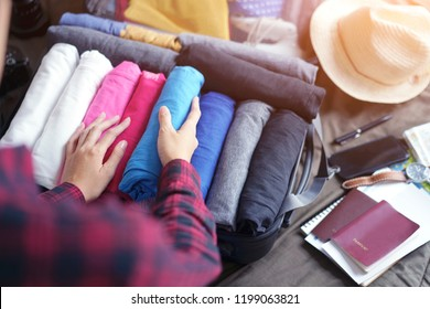 Woman hands pack clothes in suitcase bag on bed, prepare for new journey and travel to long weekend.