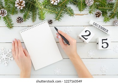 Woman hands with pen and blank notebook. Christmas decoration Fir tree, Pine cones and perpetual calendar 25 december on white background Flat lay frame mockup. Minimal design