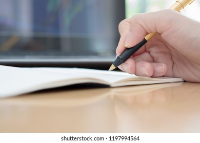 Woman hands with pen writing on notebook in the office