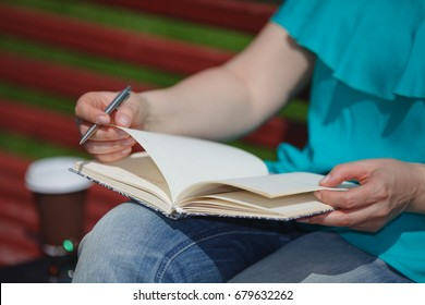 woman hands with pen writing on notebook in park
