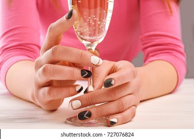 Woman hands with perfect design manicure. Young woman with beautiful black and white matte nails holding glass of champagne close up. Female beauty and elegance.