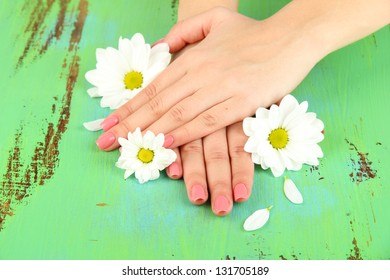Woman hands with pink manicure and flowers, on color background