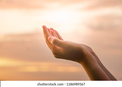 Woman hands place together like praying in front of nature ocean and blue sky  background.