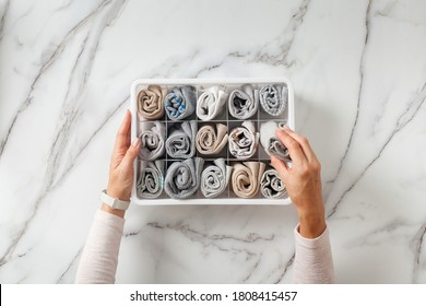 Woman hands placing wardrobe drawer organizers with full of folded underwears. Sock drawer with folded socks. Perfect and neatly setting of clothes. Linen drawer organization solution. Perfectionist.
