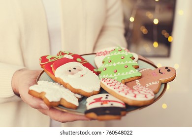Woman hands with plate full of christmas gingerbread cookies close up