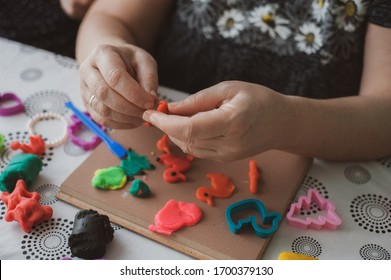 Woman hands playing with colorful clay, plasticine.