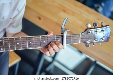 Woman hands playing guitar with a capo