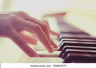 woman hands playing piano, selective focus,color filter