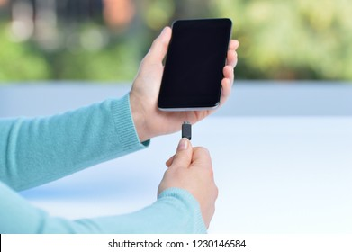 Woman hands plugging a charger in a smart phone