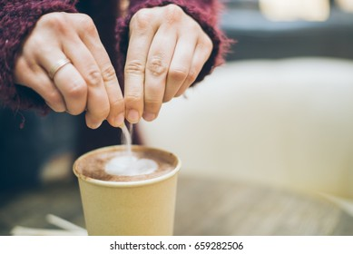 woman hands pouring sugar to the latte cup in cafe