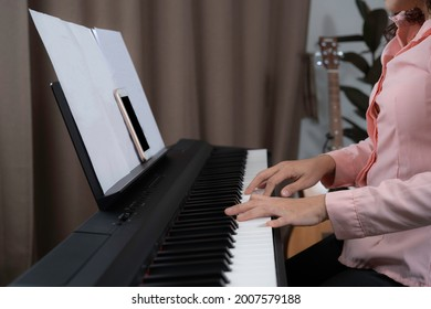 A woman hands press on electronic paino with blank sheet of paper note on note holder and smartphone with black and blank screen gor put advetisement, playing paino concept at home.