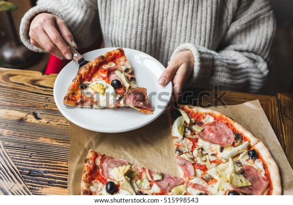 Woman hands put on a plate a piece of fresh hot pizza with ham, artichokes, olives and tomatoes