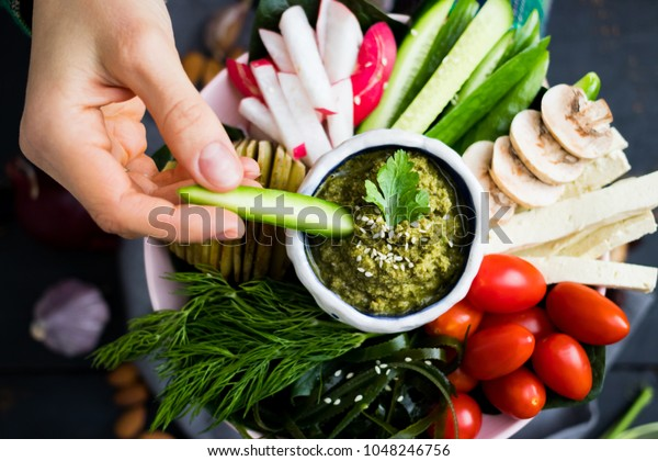 Woman hands puts cucumber to healthy veggie buddha bowl with vegetables - cheery tomatoes, radish, mushrooms, seaweed, garlic,  avocado chickpea dill dip. Above top view. Raw, vegan, vegetarian food
