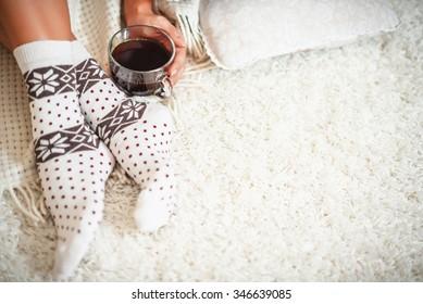 Woman hands putting on warm woolen socks.