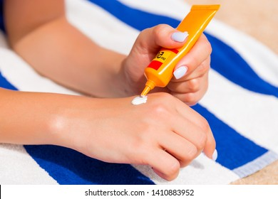 Woman hands putting sunscreen from a suncream bottle.