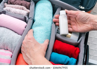 Woman hands putting towel and travel shampoo bottle to suitcase,