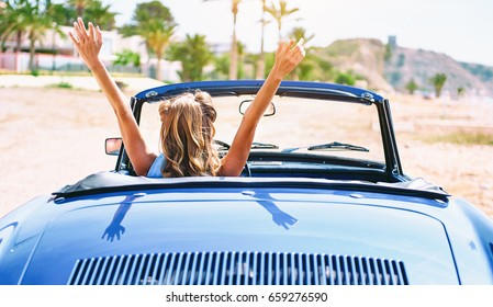 Woman with a hands raised sitting in retro cabriolet car. Back, rear view. Palm tree, tropical nature on background. Travel, tourism, adventure and journey concept, woman driver traveling. Spain