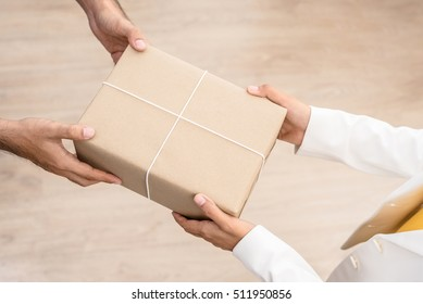 Woman hands receiving package from a man - delivery and courier concepts