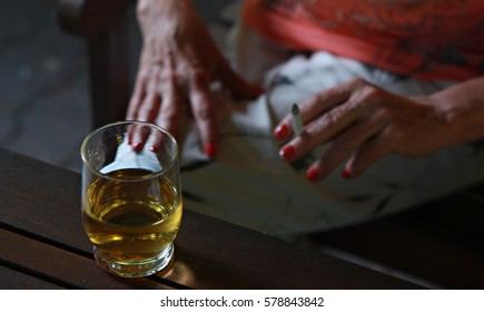 Woman hands with red manicure smoking cigarette and having vodka and apple drink