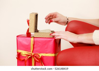 Woman hands red nails manicure opening golden gift box with jewel pearls. Christmas time, giving and happiness concept.