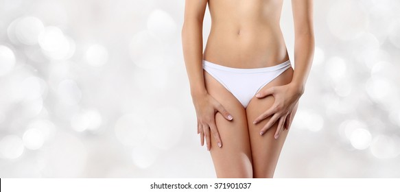 woman hands resting on the thighs isolated on blurred lights background