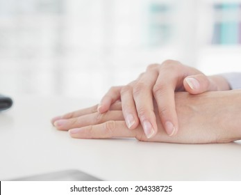 Woman hands with woman hands resting table