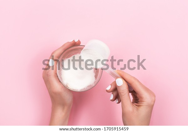 Woman hands with a scoop with collagen or protein powder and a glass of water. Trendy beauty supplement for healthy skin and bones. Flatlay, top view.