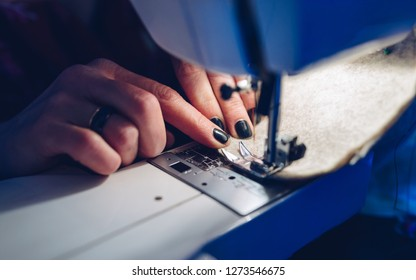 woman hands sewing fabric on sewing machine - close up