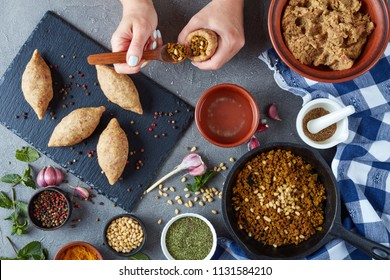 woman hands is shaping a kibbeh on a kitchen table. ground meat with bulgur in a bowl, fried minced meat with pine nuts in a skillet, spices in bowls on a concrete table, view from above, flat lay