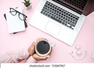 Woman hands in shirt with coffee on Pink pastel. Office desk with with laptop, notebook, phone, sheet, pencils, candy,  headphones, plant, pencils. flat lay top view concept.
