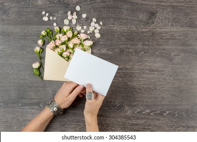 woman hands silver jewelry with romantic letter. From envelope fly overwhelm small bouquet of rose. Empty space for your text. Top view. Mockup template for gift certificate