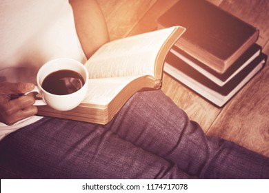 woman hands sitting on wood floor holding a cup of coffee while and reading on holy bible, blurred page, Christian background