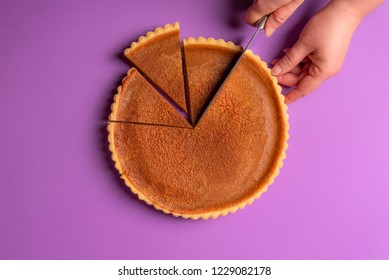 Woman hands slicing a pumpkin pie on a purple background. Minimalist culinary concept. Homemade sweet pie. Traditional holidays dessert. Top view.