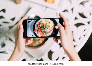 Woman hands take photography of food with smart phone in restaurant,Smartphone photo for social network post.