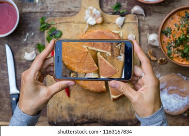 Woman hands take smartphone food photo. Make phone food photography for blogging and social media in top view trendy style. Georgian suluguni cheese traditional food.