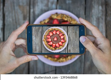 Woman hands take smartphone photo of food. Phone photography of food for blog, social media. Chocolate homemade dessert with oats, strawberry. Sweet cake.