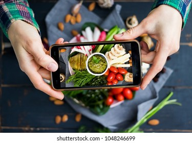Woman hands takes food photo of mixed healthy veggie buddha bowl with vegetables and avocado chickpea dip. Make food photography for social networks on mobile smartphone. Raw, vegan, vegetarian food