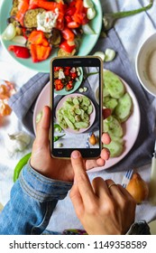 Woman hands takes smartphone food photo of cucumber salad for lunch. Makes food photography for social networks or blogging with phone. Raw, vegan, vegetarian food