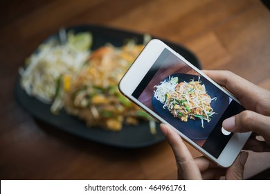 Woman hands taking food photo by mobile phone