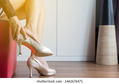 Woman hands taking off high heel shoes because suffering from feet pain