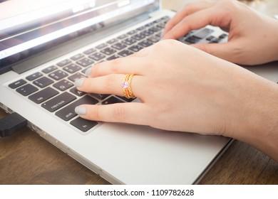 woman hands taping on laptop keyboard