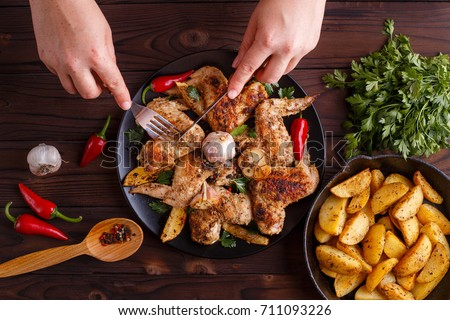 Woman hands tasting grilled chicken wings. Hot fresh appetizing countryside food. Cooking concept, meat dishes, homemade cuisine