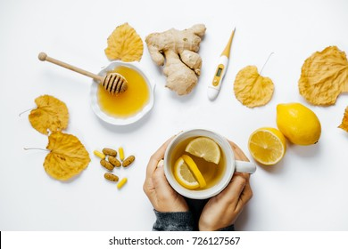 Woman hands with tea, lemon, thermometer, ginger, honey, tablets and dry leaves on a white background. flat lay.