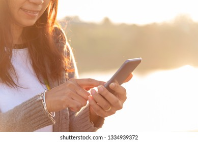 Woman hands texting smartphone mobile using cellphone with smart technology lifestyle. woman social addict communicate by internet on sunrise